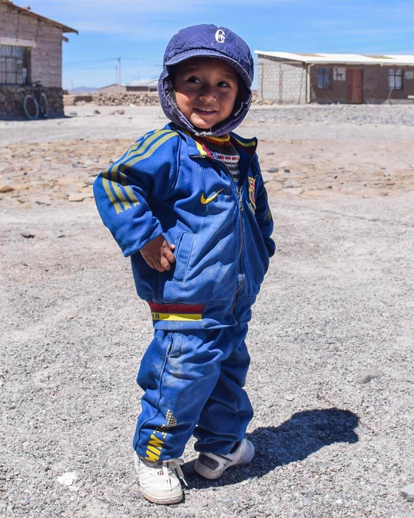 A child poses for a photo at a ssalt mining town on te salt flats of Bolivia