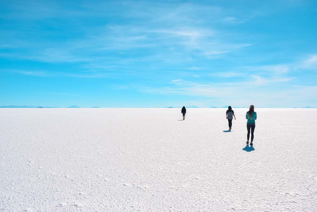 3 people walk on the salt flats in Bolivia showing just how large they are