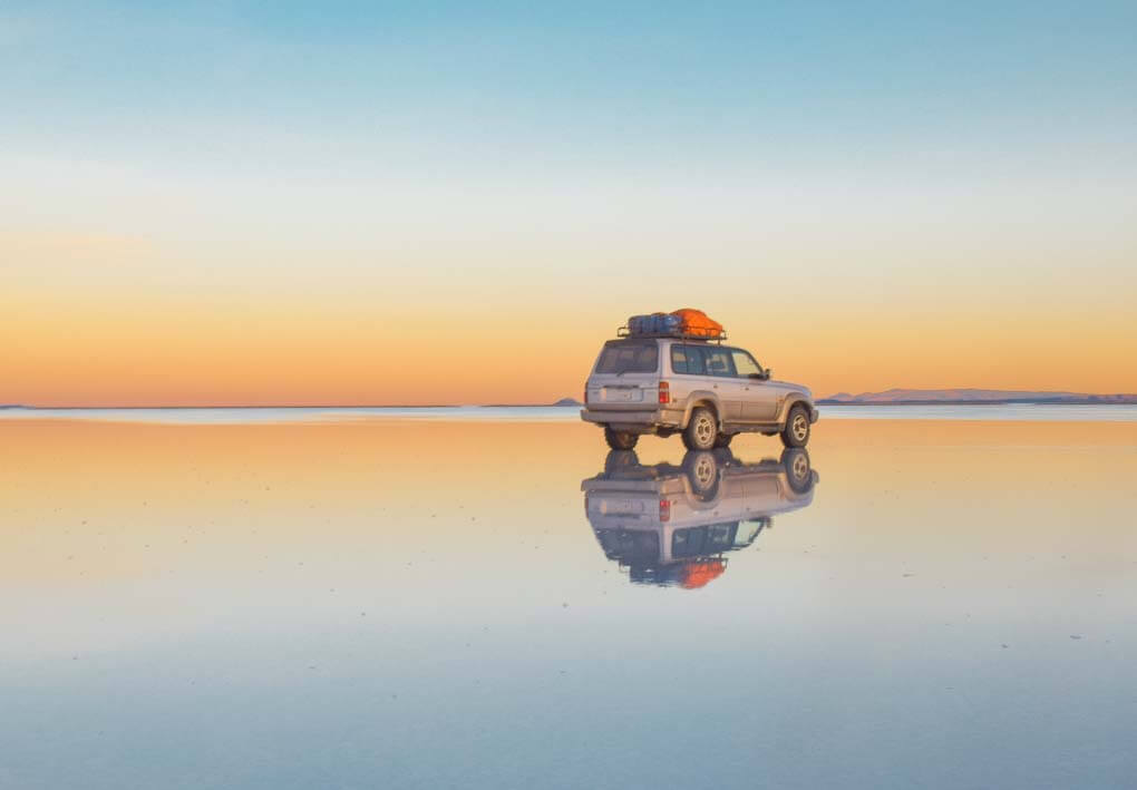 A 4wd sits in the water on the salt flats and shows how amazing the reflections are during the rain season