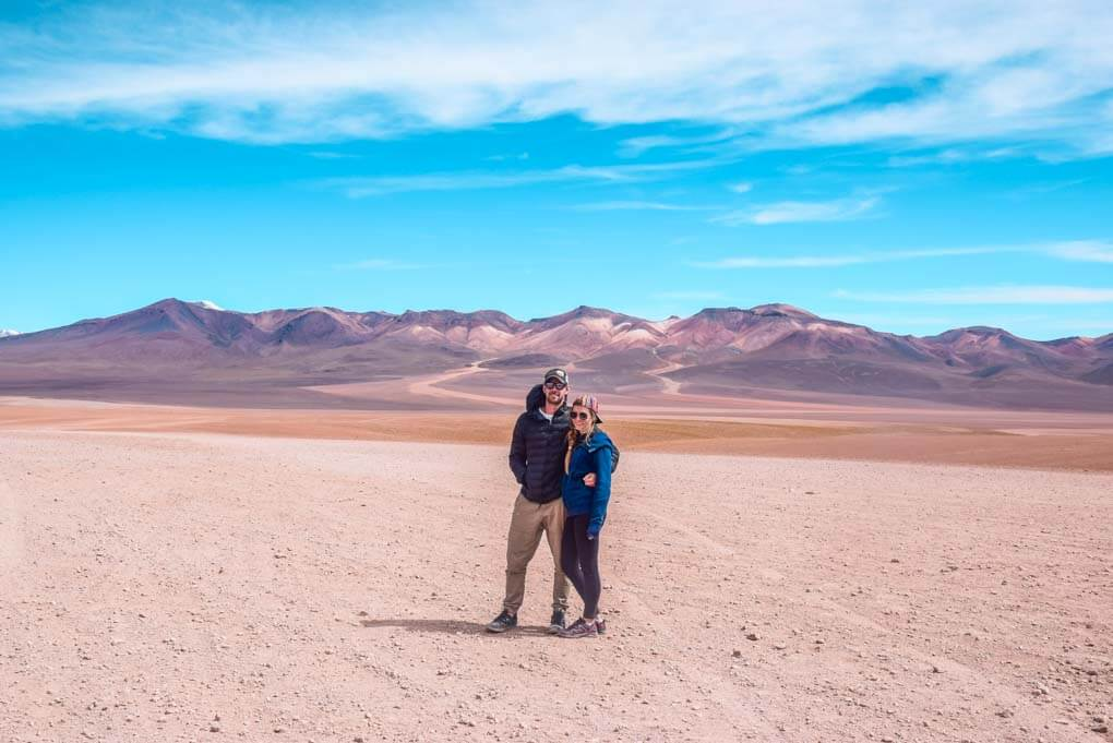 Bailey and Daniel pose for a photo on a desert area of the salt flats in Bolivia