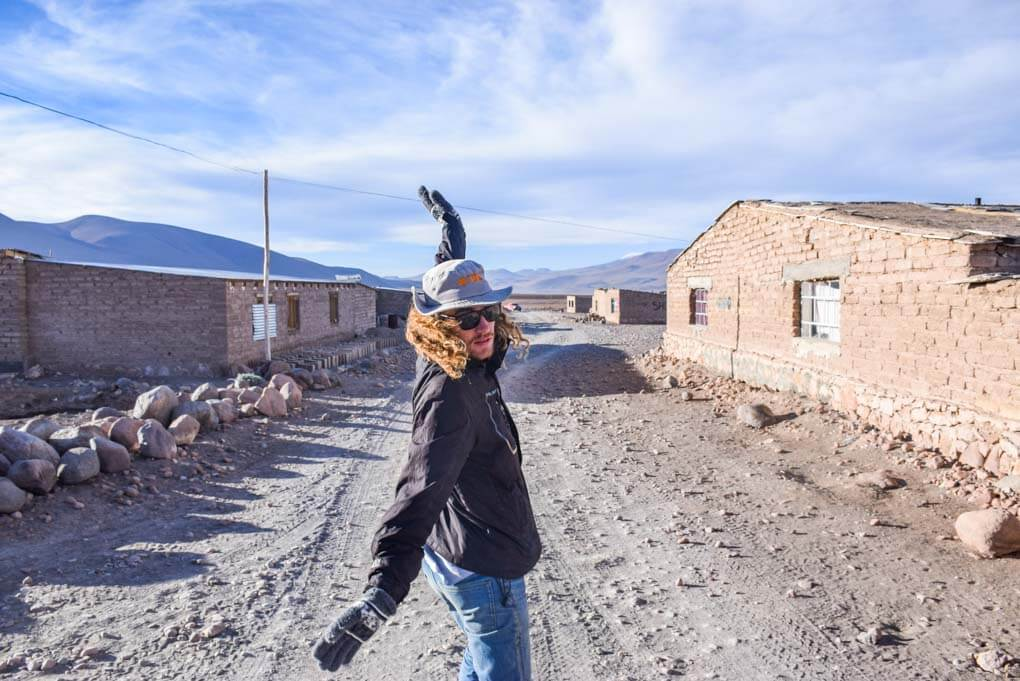 A man makes a silly pose while in one of the towns in the salt flats. Here you can buy food.