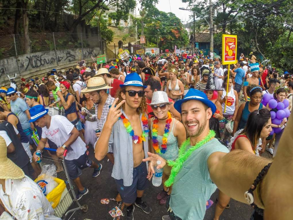 Daniel, Bailey and a fried of theres take a selfie in the middle of a bloco party during Carnival in Rio de Janeiro, Brazil