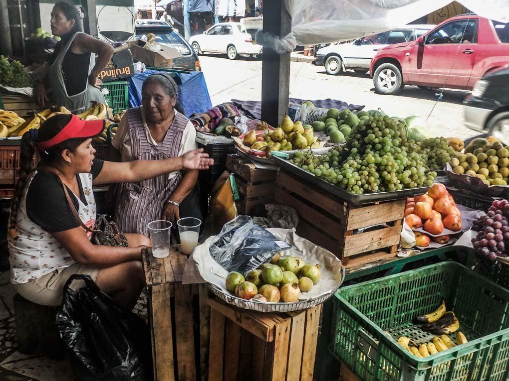 Two ladies sell vegetables in a market in Santa Cruz, Bolivia