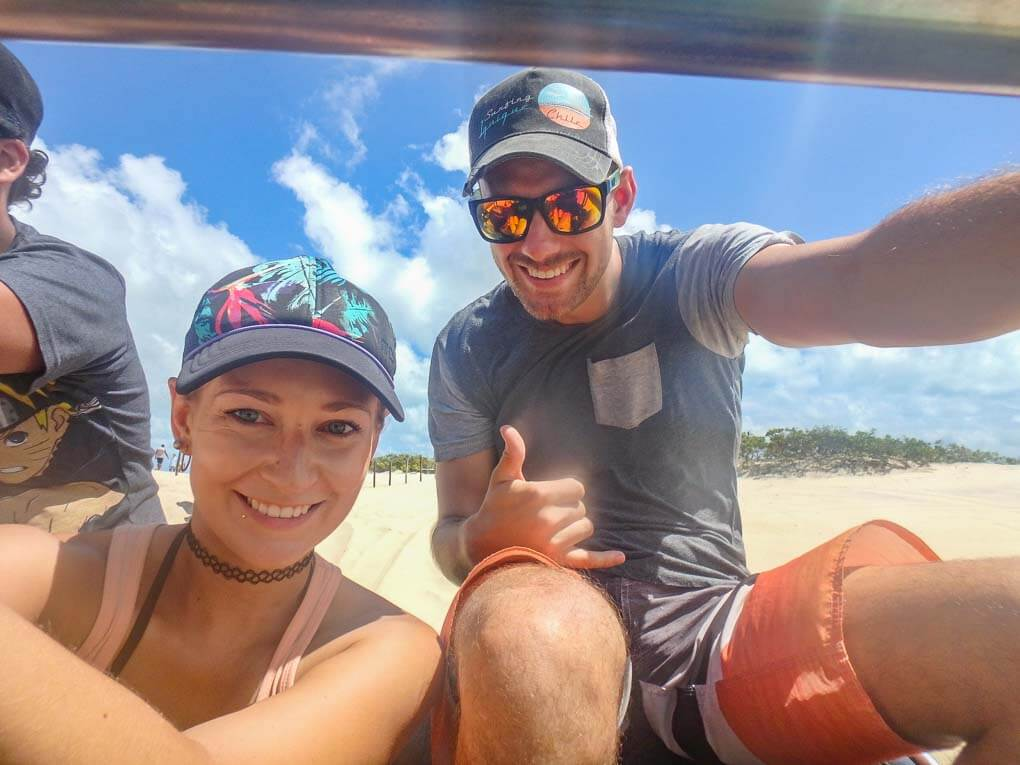 Bailey and Daniel sit on the back of a Dune buggy in Brazil