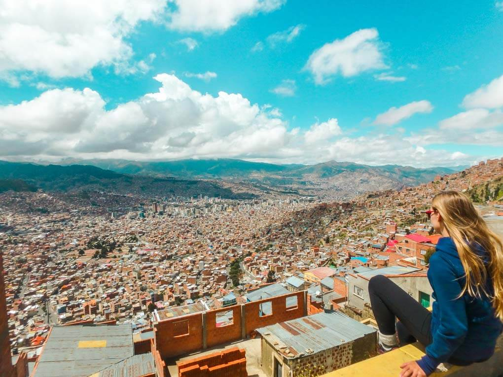 bailey sits at the viewpoint at the top of the gondola in La Paz looking over the city