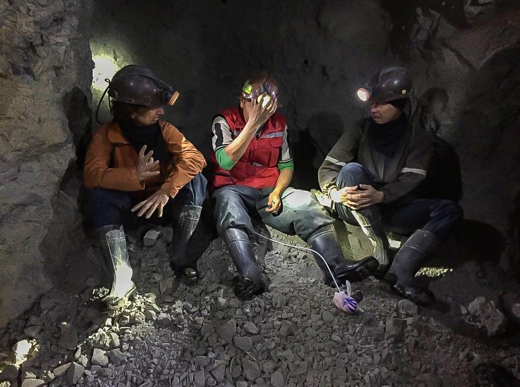 Three men sit in the Cerro Roco mine in Potosi, Bolivia