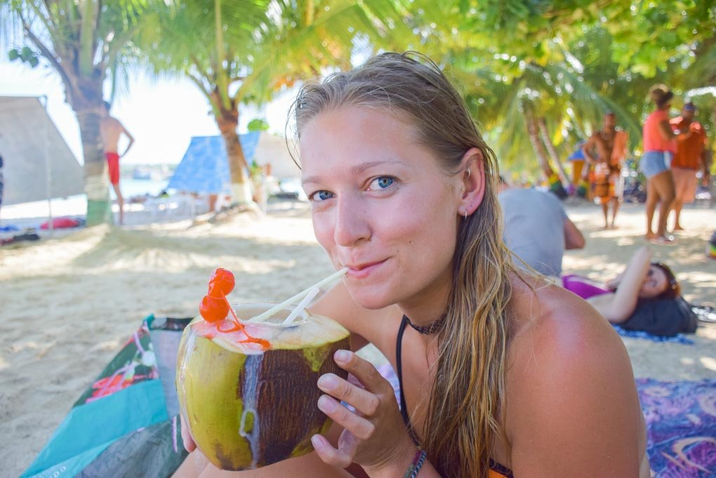 Bailey drinking coconut water on the beach
