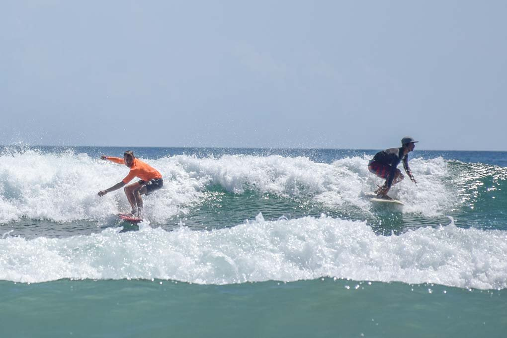 two people surfing a wave in Sa Juan del sur