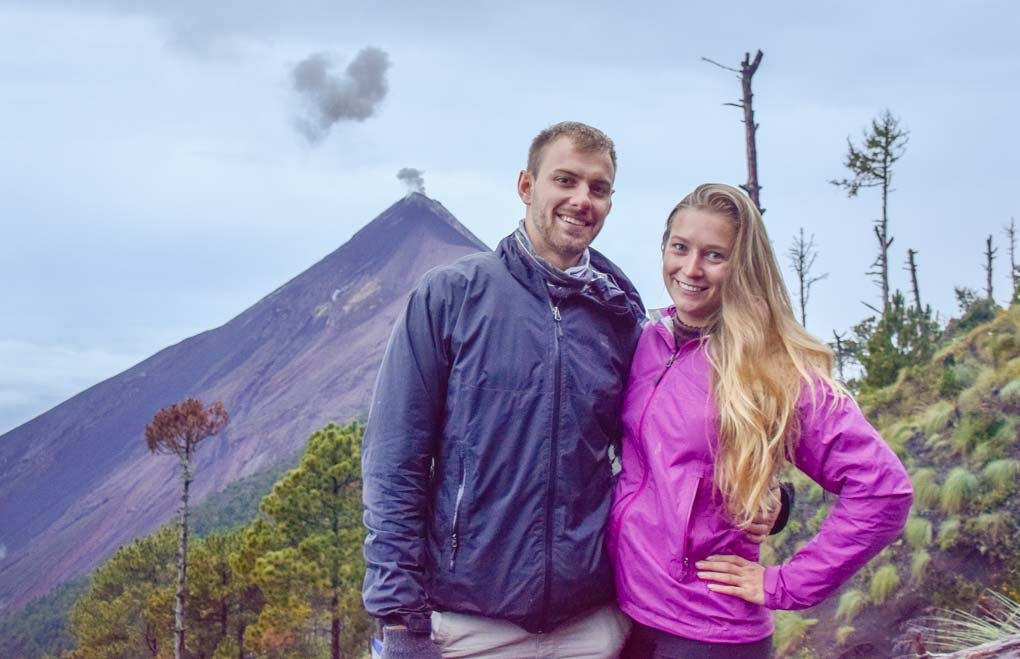 Bailey and Daniel take a photo with Fuego volcano erupting in the background along the acatenango volcano hike