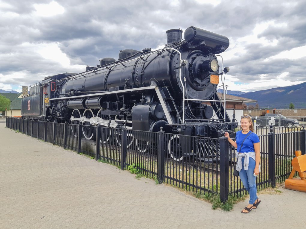 bailey takes a photo with the old train in Jasper