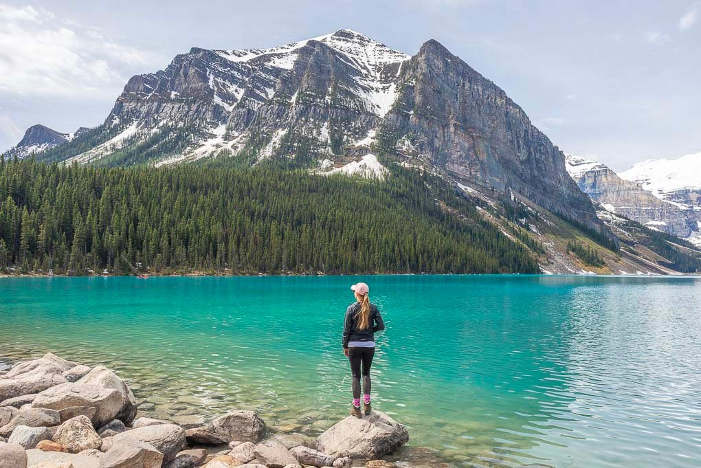 A lady stands at the Lake Louise forshore