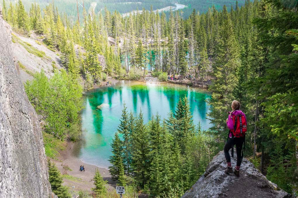 A lady stands on a rock overlooking the Grassi Lakes in Canmore, Canada