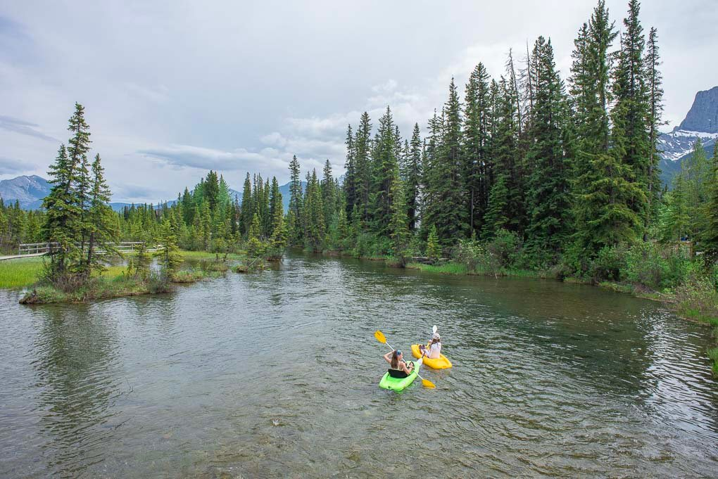 Two people kayak in Spring Creek, Canmore