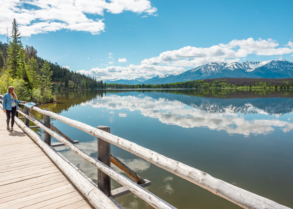 A lady walks the Pyramid Island boardwalk in Jasper National park on a sunny day admiring the reflections on the lake