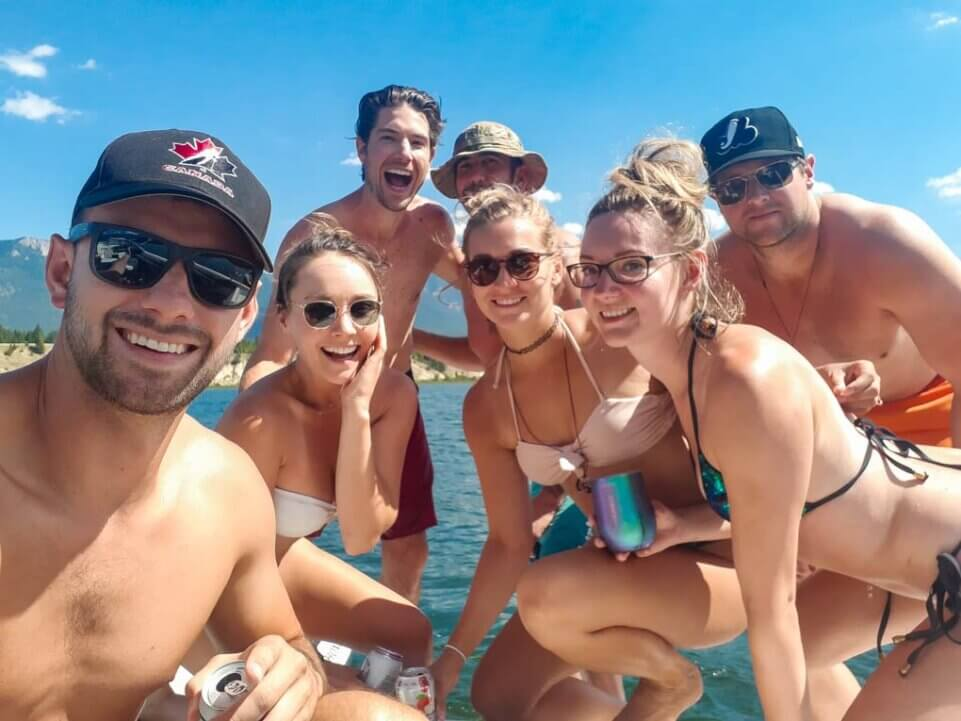 A group of people take a selfie on their boat on Lake Windermere, BC