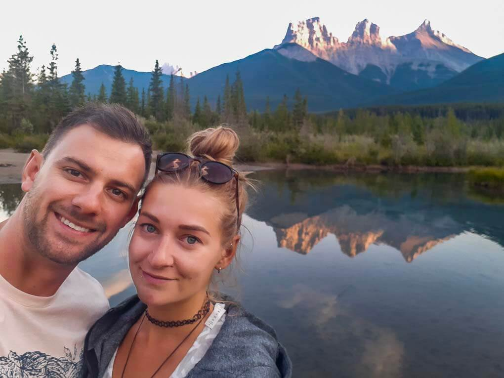 Bailey and Daniel take a selfie with the Three Sisters Mountain Range in the background in Canmore