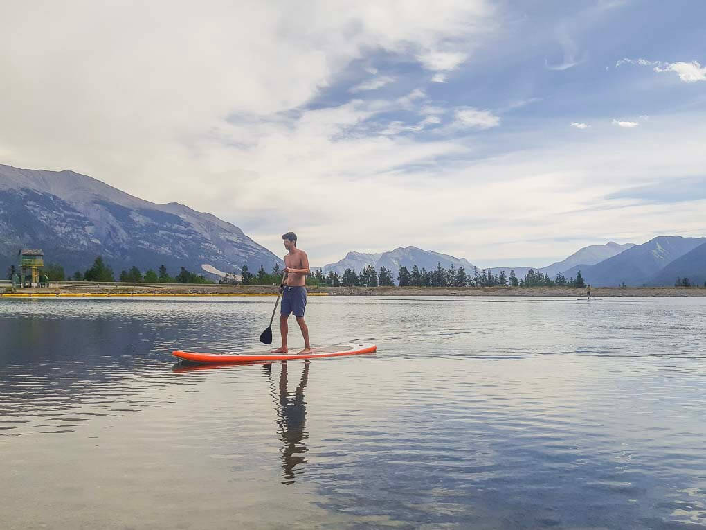 A man paddleboards at Rundle Forebay Reservoir in Canmore