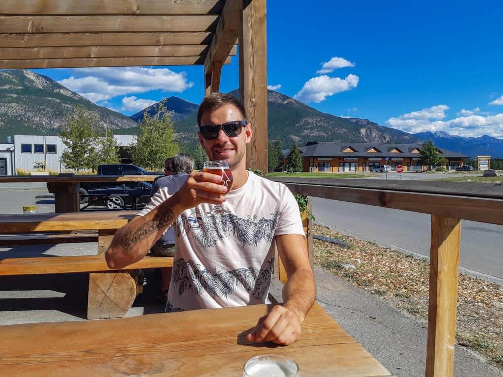 A man enjoys a beer at Arrowhead Brewing in Invermere, BC