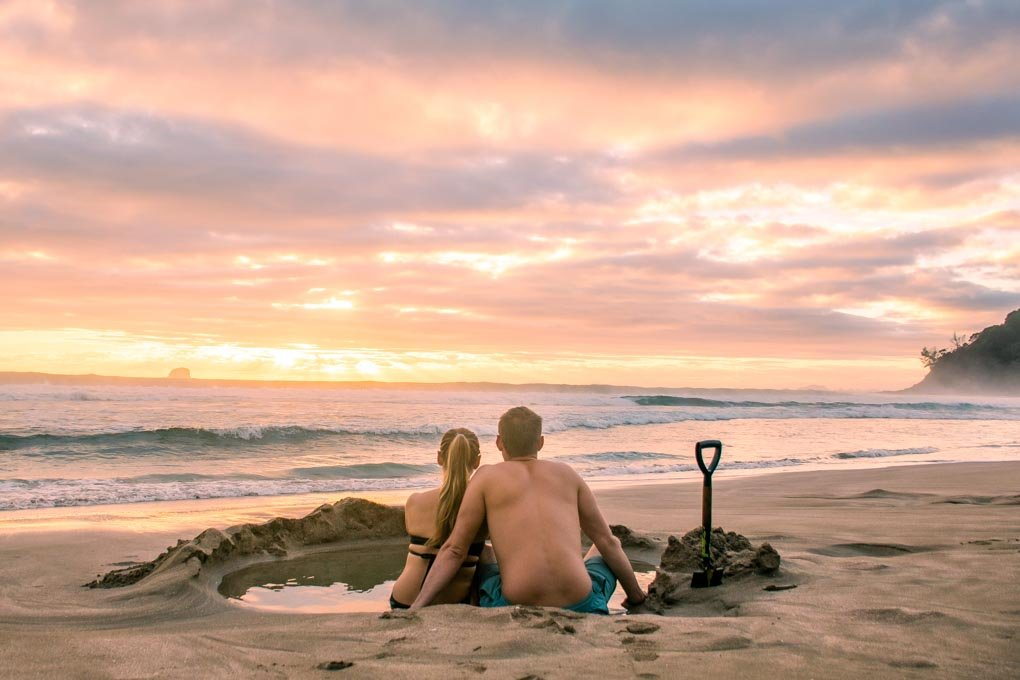 A couple relax at Hot Water beach in New Zealand