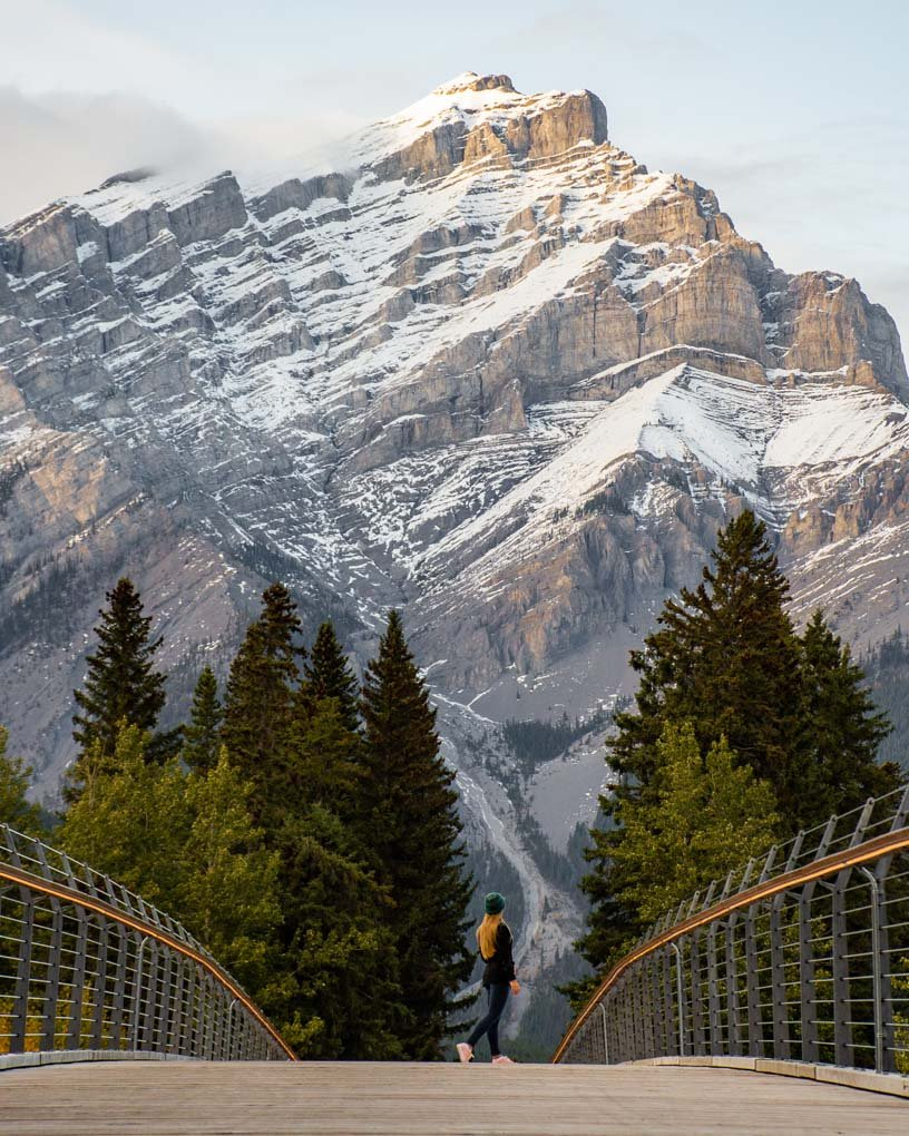 A lady walks along the Banff Pedestrian Bridge taking a photo for Instagram