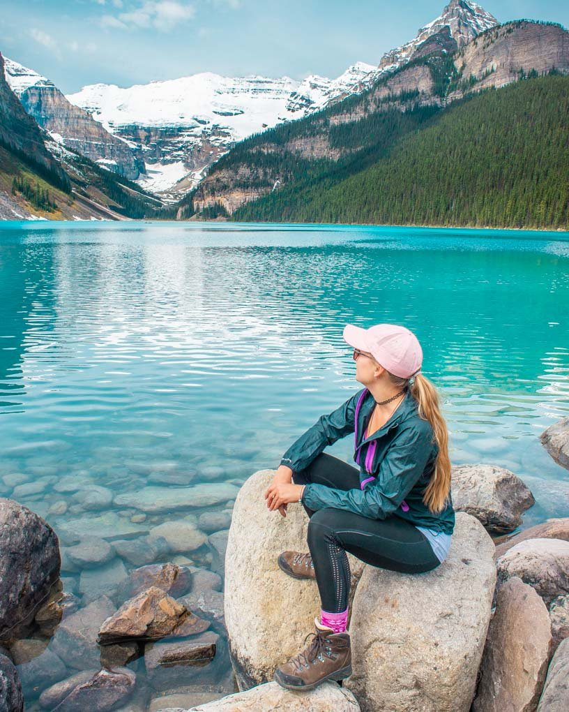 A lady sits on a rock at Lake Louise looking out over the water at the glacier and mountains