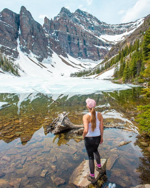 A lady stands on a rock in Lake Agnes and poses for a photo while staring out at the mountains on a sunny day in Banff National Park