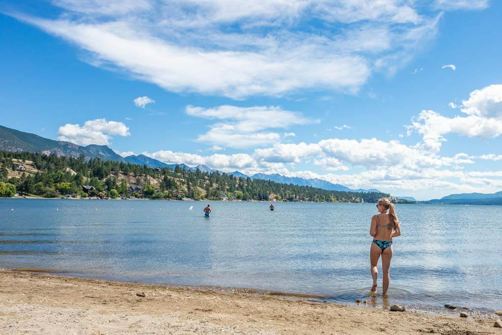 A lady walks into the water at James Chabot Provincial Park in Invermere, BC