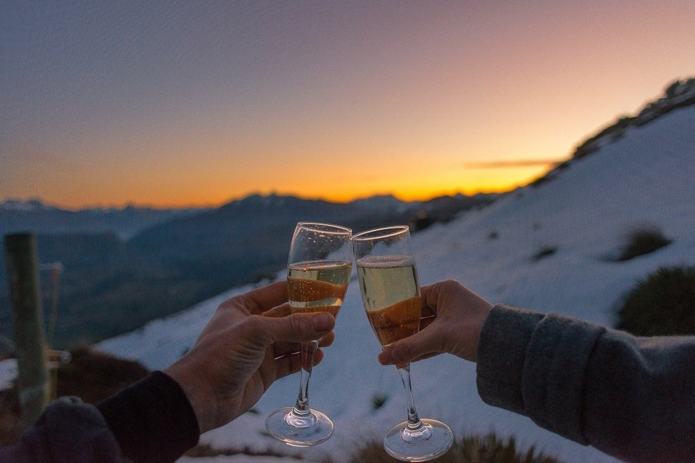 two glasses cheers at sunset on a mountain during a honeymoon holiday in New Zealand