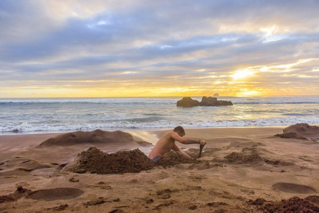 A man digging a hole at Hot Water Beach