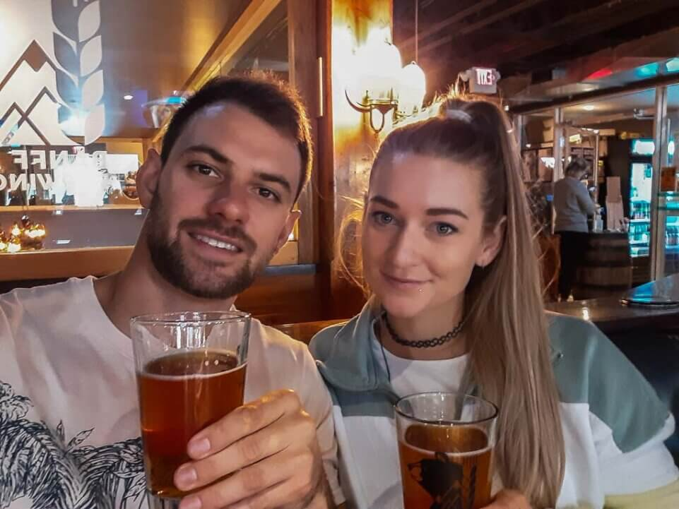 A couple take a selfie with beers at the Banff Brewery in Banff