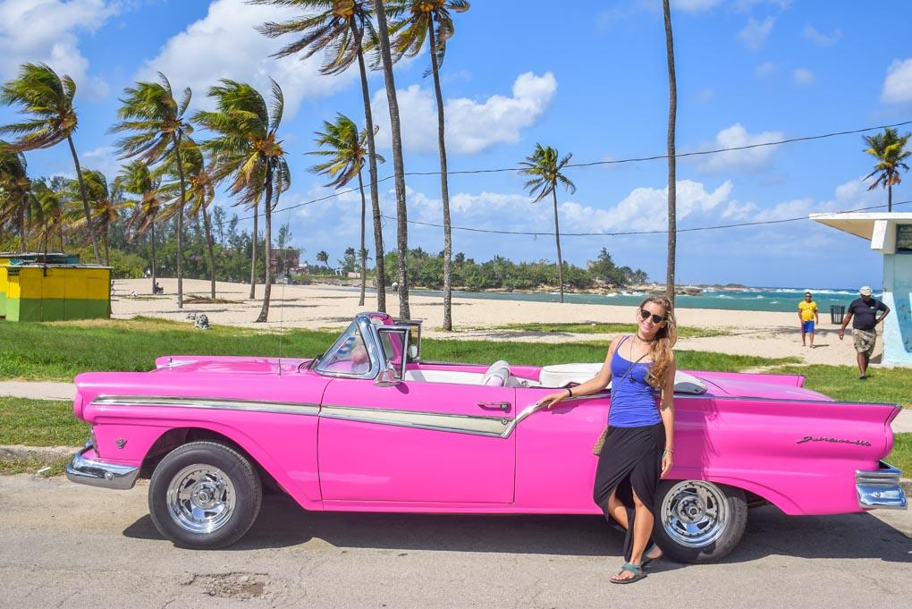 A lady poses with a vintage car at Playa del Este, Havana