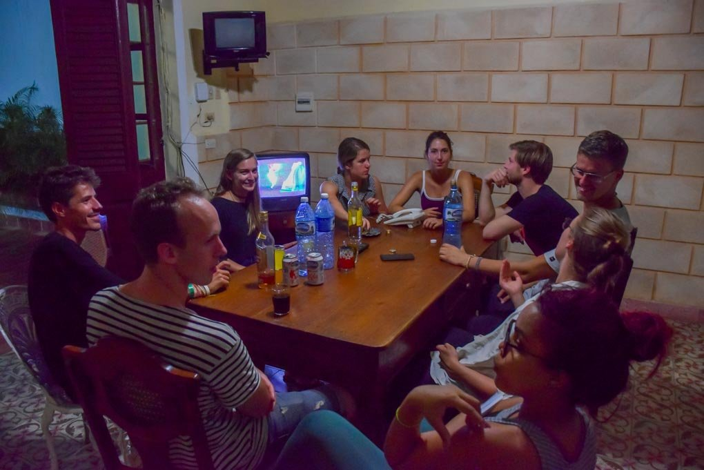 A groupd of people drink rum at a Casa Particular in Havana