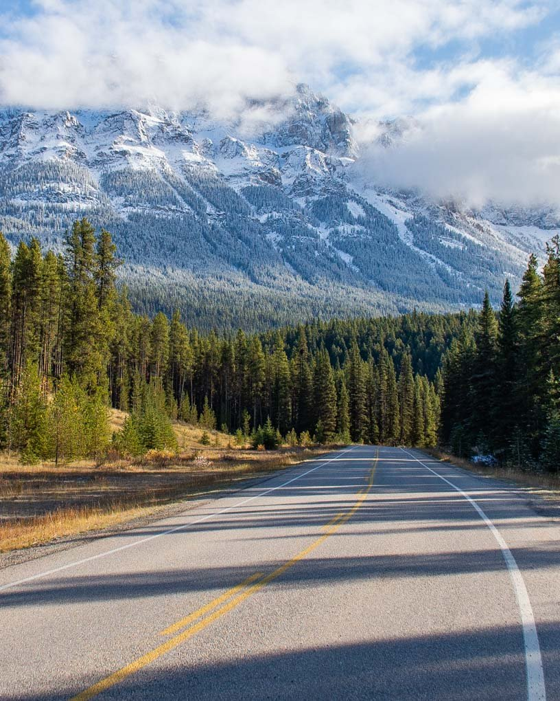 A view of the road with mountains in the background on the Bow Valley Parkway in Banff National Park