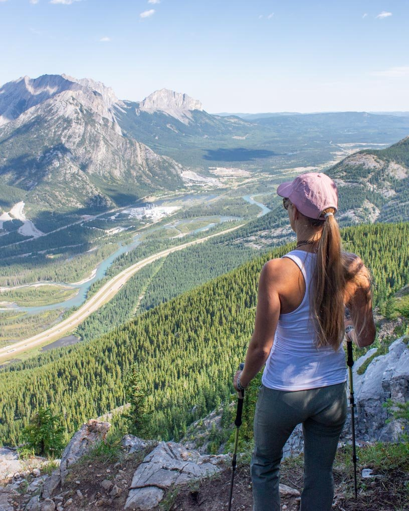 A lady stands with her hiking poles looking at the views from the Heart Mountain trail