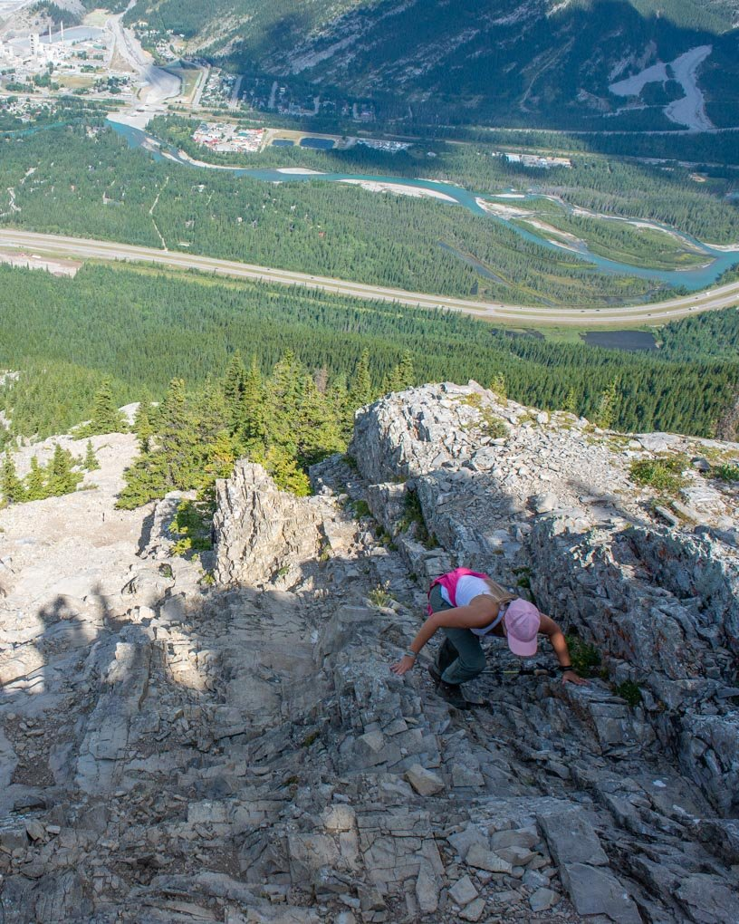 A lady on her hands scrambles up Heart Mountain on the Heart Mountin loop