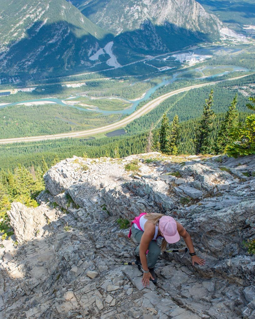 A lady on her hands climbing up Heart Mountain Trail