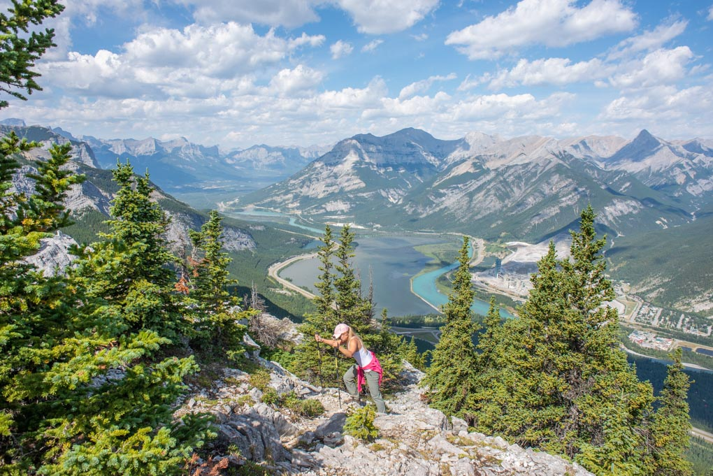 A lady climbs up rock on the Heart mountain hike near Canmore, Alberta