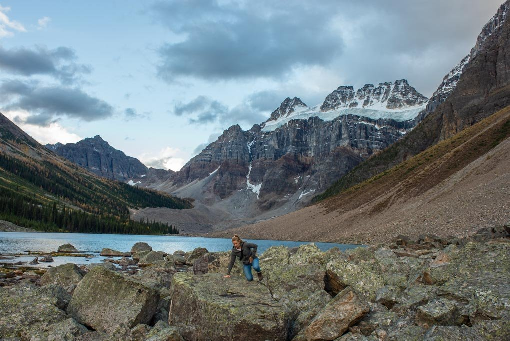 A lady climbs over a boulder on the Consolation Lakes Trail near Lake Moraine