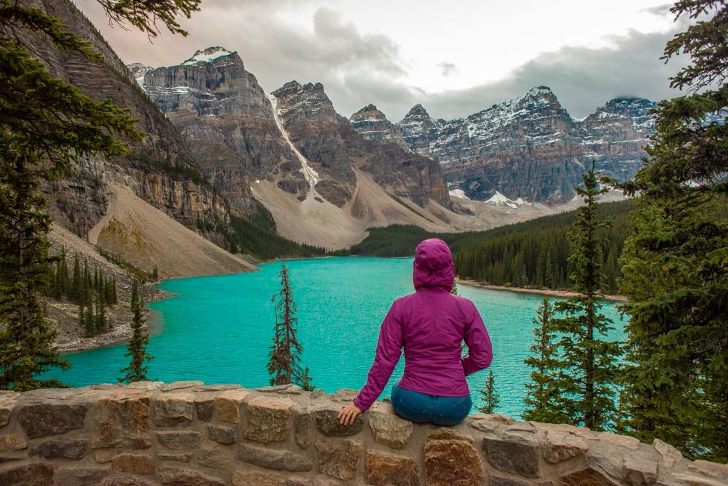 A lady sits on a rock wall at the Rockpile at Moraine Lake in Banff