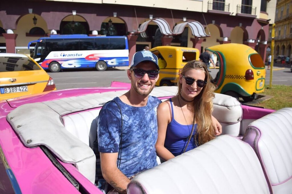 sitting in a hot pink vintage car in Havana, Cuba