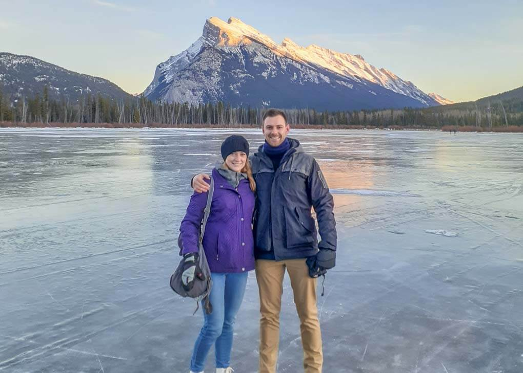 Bailey and Daniel from Destinationless Travel pose for a photo on a frozen lake