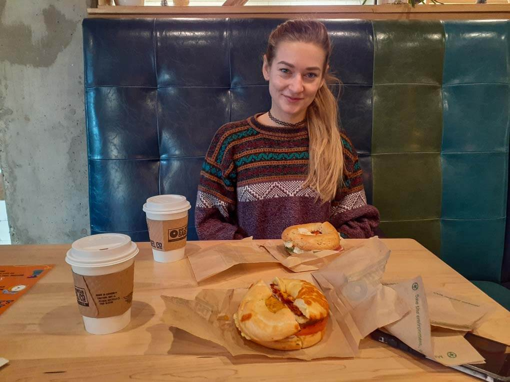 A lady poses for a photo with her bagel from Rocky Mountain Bagel Company