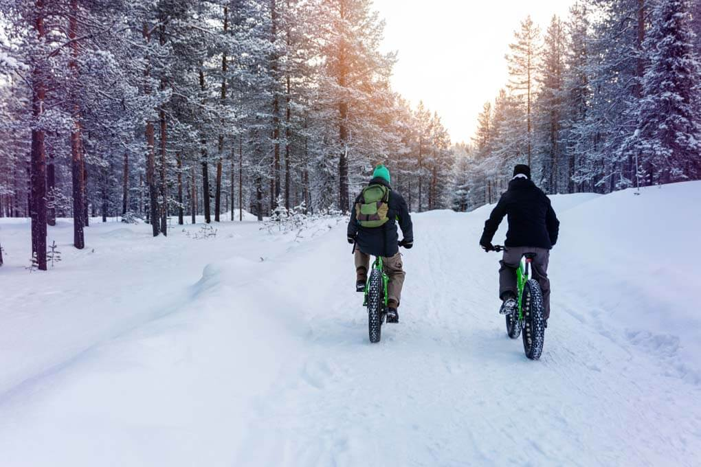 Tw people go fat biking through the snow