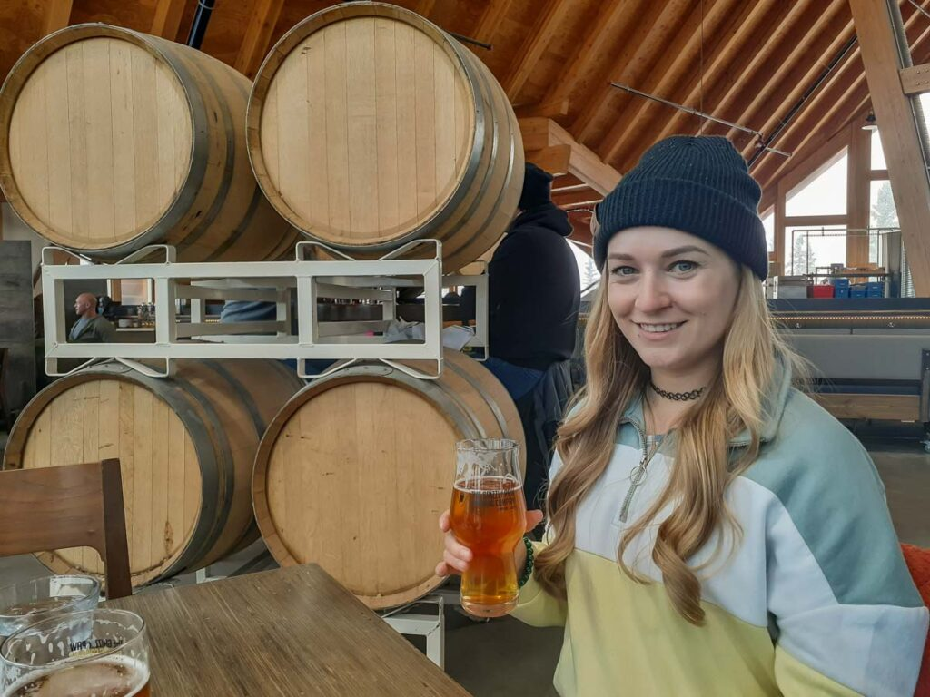 girl drinking beer at the Girzzly Paw in Canmore in winter