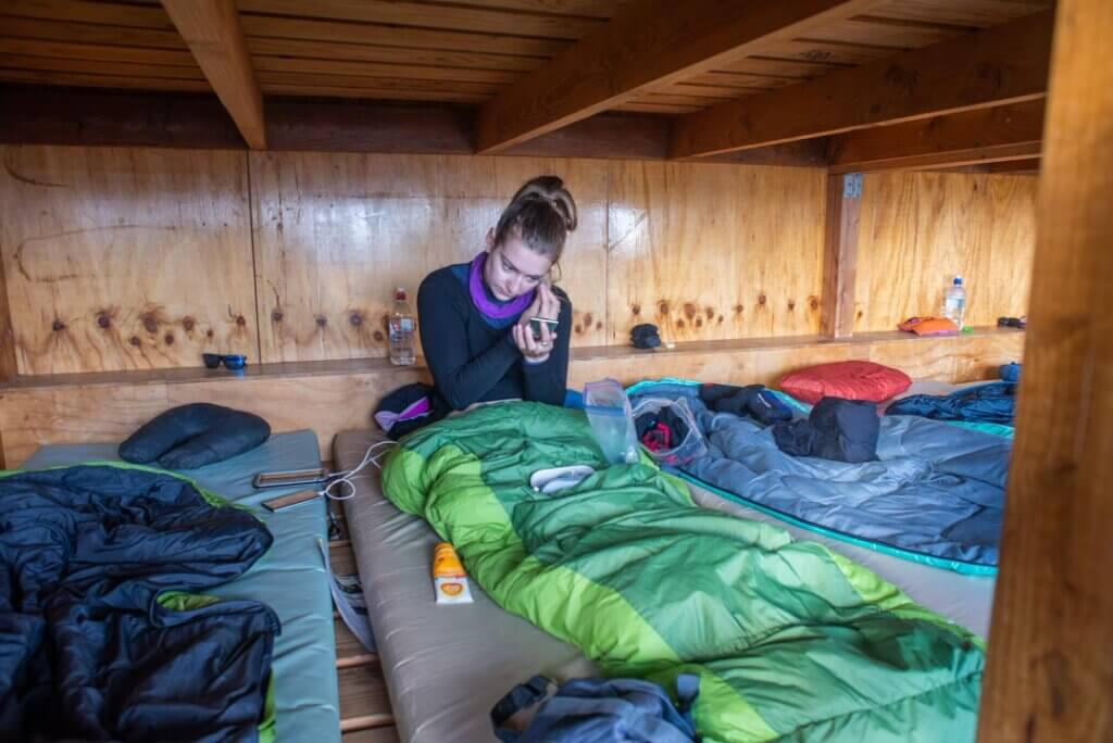 woman in a sleeping bag in a bunk bed withing a new zealand hut