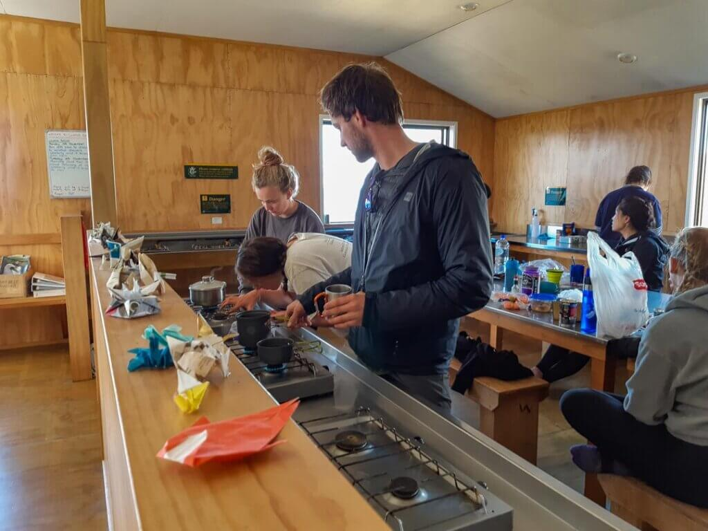 People cooking in the Luxmore Hut, New Zealand