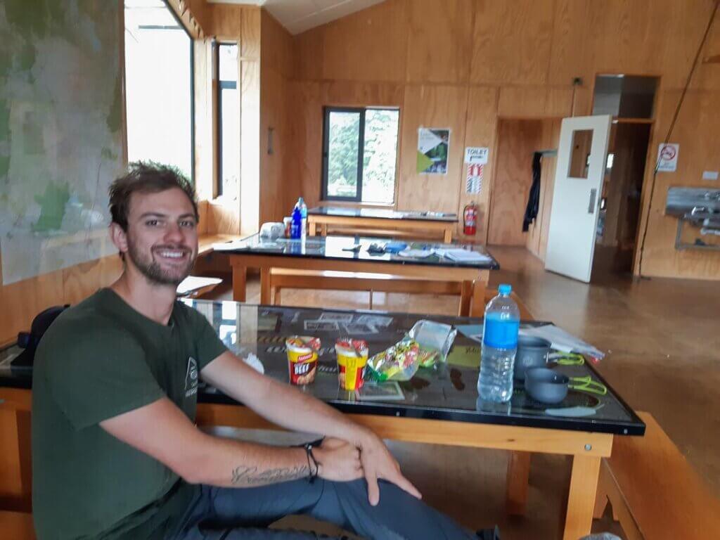 Daniel sitting at a table at the Waihohonu Hut