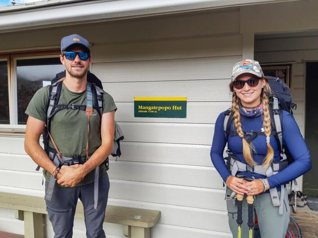 two people standing outside a hut in New Zealand