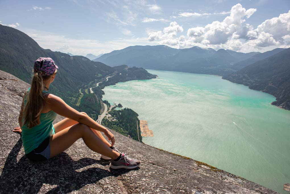 A lade sits at the top of the Stawamus Chief hike near Vancouver, Canada