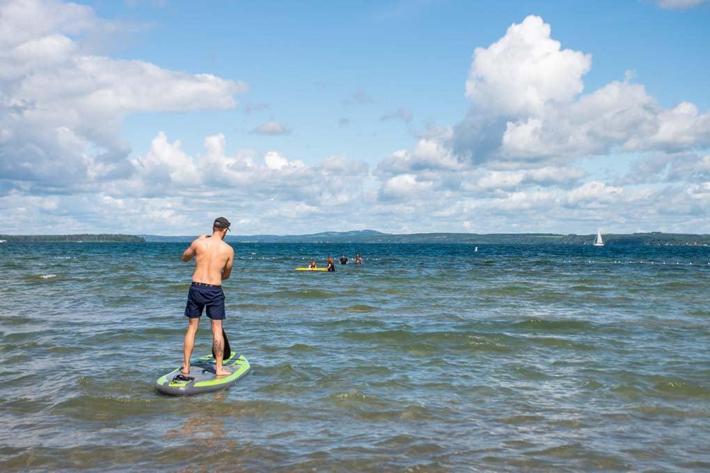 Man paddleboarding out on Sylvan Lake, Alberta